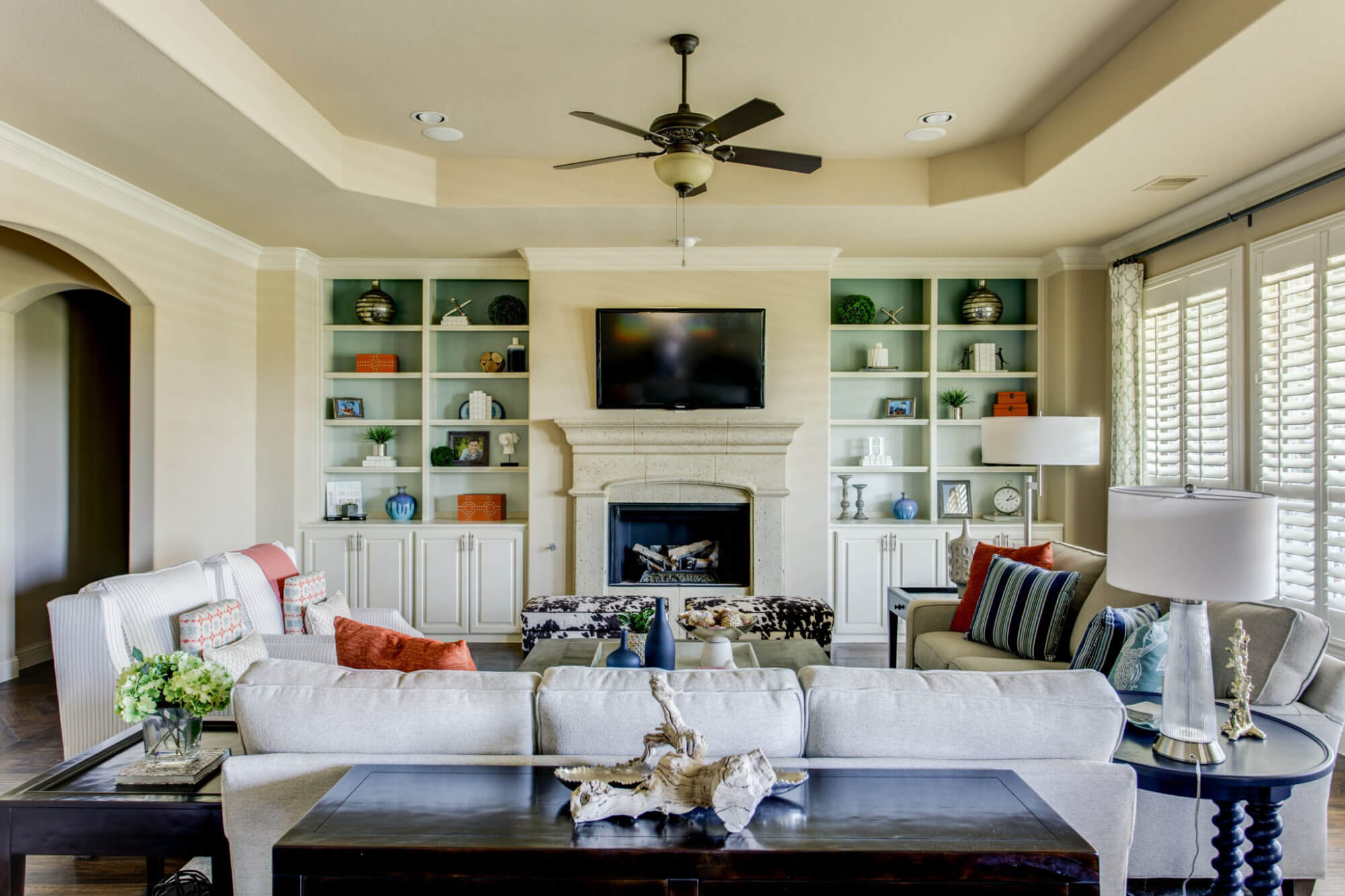Living room with vaulted ceilings, built in shelving, and large, neutral sofas for extra seating. | ML Interiors Group