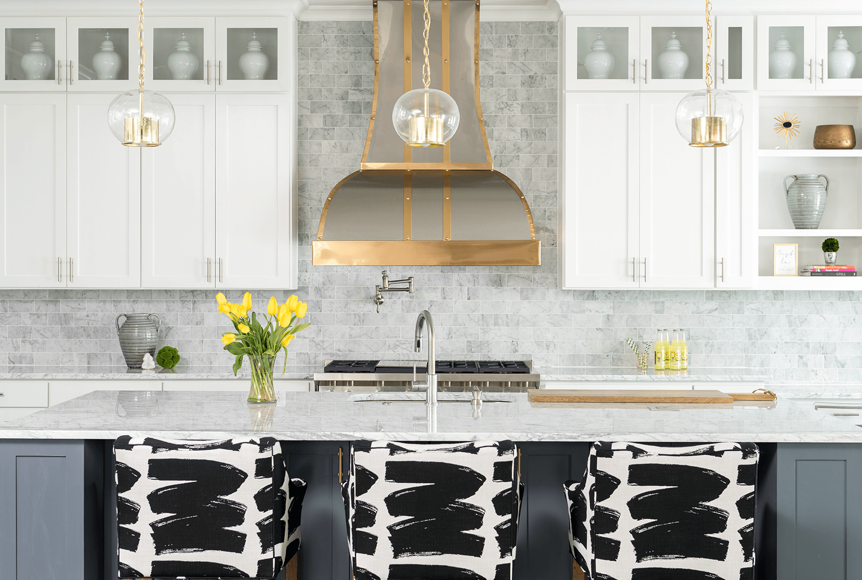 Kitchen Remodel with grey island, marble countertops, marble subway tile back splash, gold trimmed vent hood, white cabinets, and custom perrinials barstools. | ML Interiors Group