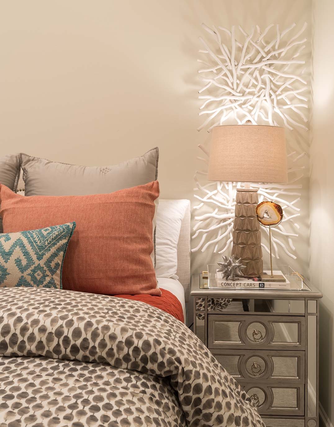Master Bedroom with coral and taupe bedding, mirrored bedside tables, and coral wall accent art for extra lighting. | ML Interiors Group