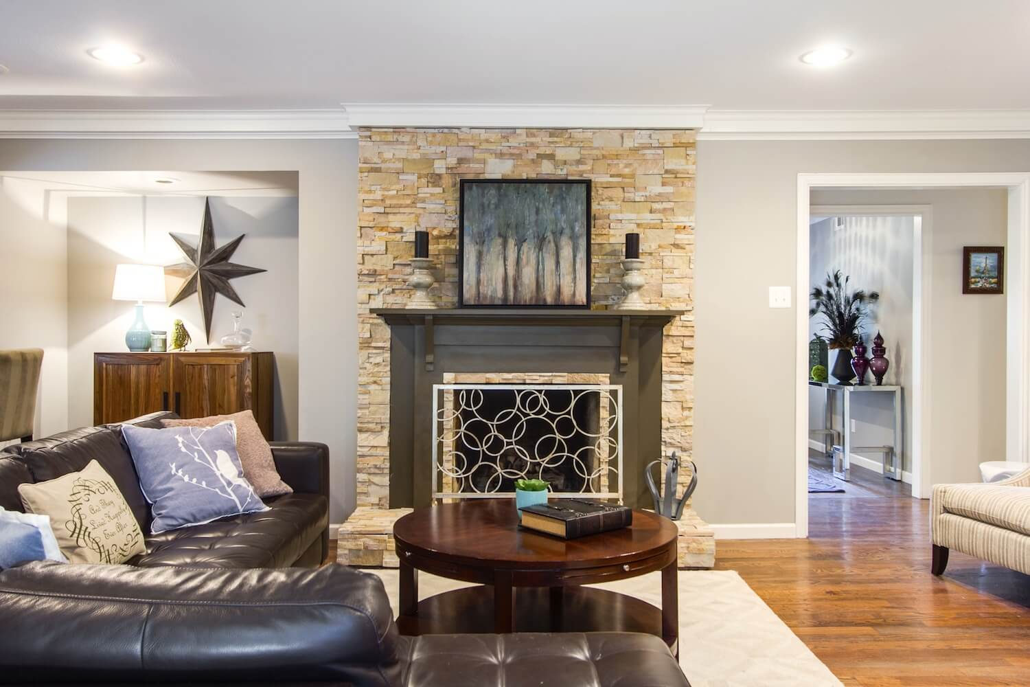 Living room with central stone fireplace, round coffee table, and a black leather L-shaped sofa. | ML Interiors Group