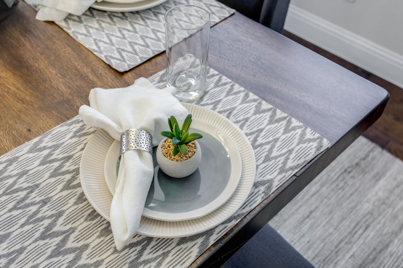 Table setting with grey printed placemats, cream and blue dinner and salad plate, white napkins with silver napkin ring and a personal succulent for each guest. | ML Interiors Group