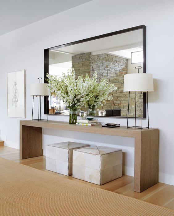jaqui seerman entry design with a black framed mirror, a natural wood console table with hide covered seating and a natural jute rug. | ML Interiors Group