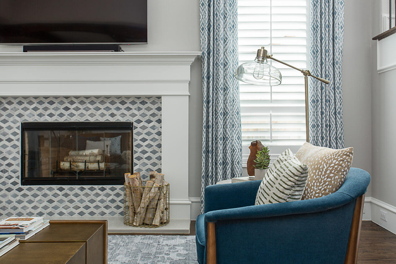 Living Room with custom curtains, a waterfall wood living room table, a custom leather sofa, and soft blue arm chairs. | ML Interiors Group