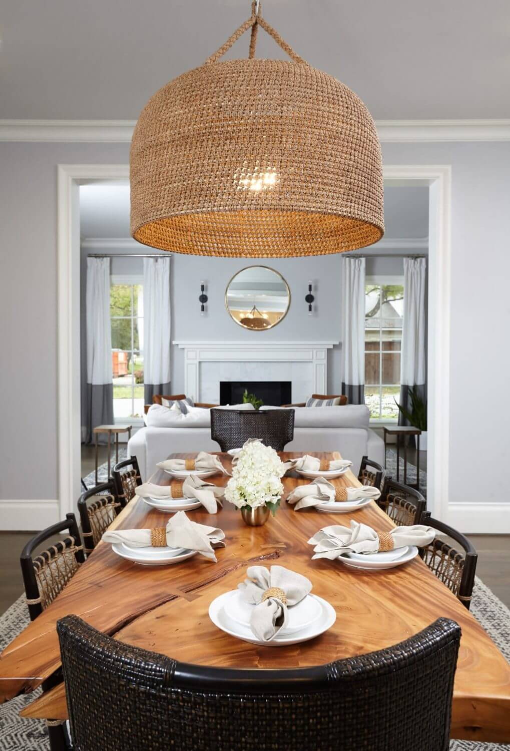 Looking past the gorgeous formal dining live edged table and oversized chandelier into the comfortable sitting room for after dinner drinks | Midway Hollow | Interior Design firm ML Interiors Group