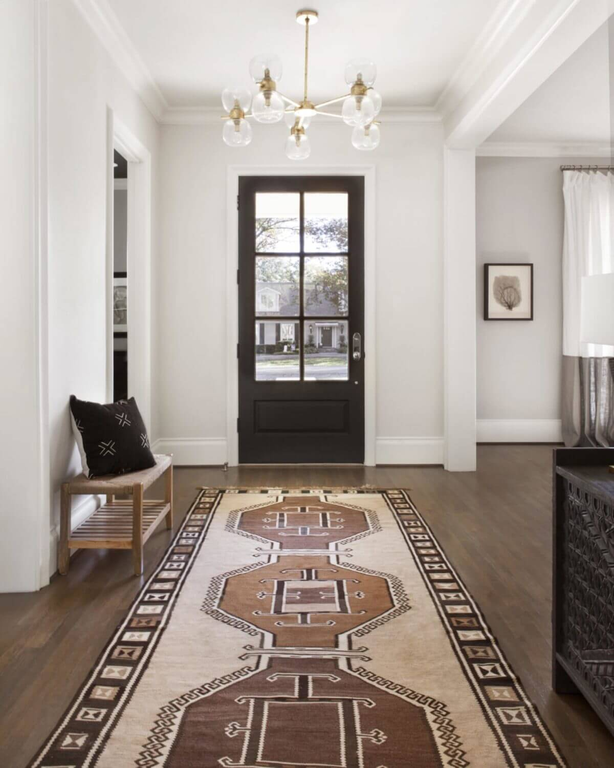 A welcoming Turkish rug, natural wood bench and brushed gold chandelier make a beautiful statement in this Midway Hollow home | Dallas interior designer, ML Interiors Group