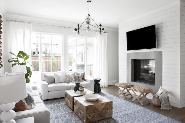Casual living room design with shiplap fireplace, chandelier and wooden accents. | Dallas interior design | ML Interiors Group